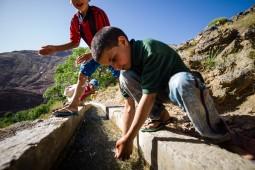 Die kinder spielen und drinken wasser aus der Quelle