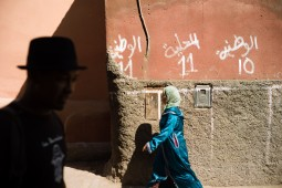 Woman walking along the street of the medina in front of electoral display