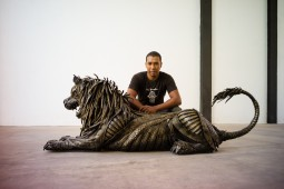 lahcen iwi a tires scupltor, posing with his Lion